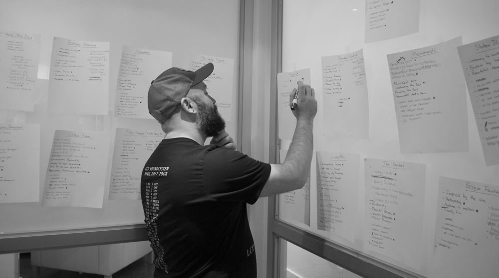 A man writing on a piece of paper taped to the wall